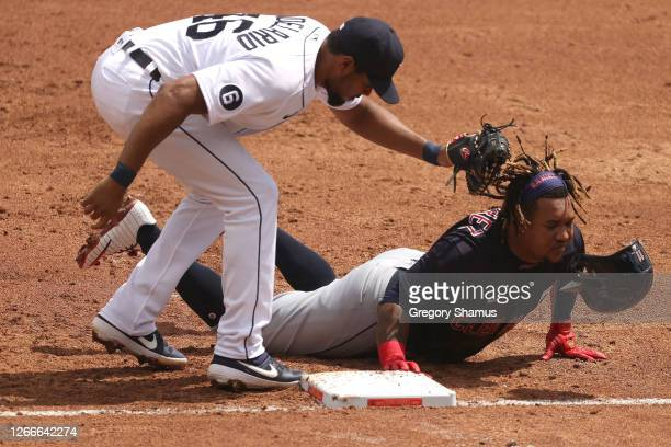 Jose Ramirez of the Cleveland Indians makes it back to first base to beat the tag from Jeimer Candelario of the Detroit Tigers during the third...