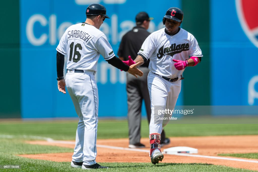 Jose Ramirez #11 of the Cleveland Indians slaps hands with third base coach Mike Sarbaugh #16 after hitting a two-run home run during the first inning against the Houston Astros at Progressive Field on May 27, 2018 in Cleveland, Ohio.