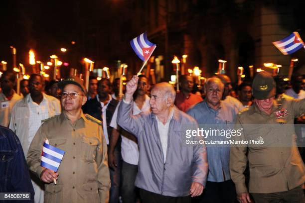Jose Ramon Machado Ventura Cuba´s first vice president waves a Cuban flag as he leads a march of thousands of Cuban students holding torches in the...