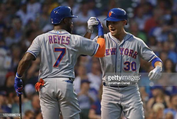 Jose Reyes and Michael Conforto of the New York Mets celebrate Confortos' home run in the 2nd inning against the Chicago Cubs at Wrigley Field on...