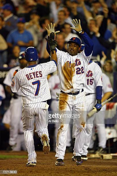 Jose Reyes and Michael Tucker of the New York Mets celebrate scoring on a two RBI hit by Paul Lo Duca in the seventh inning during game six of the...