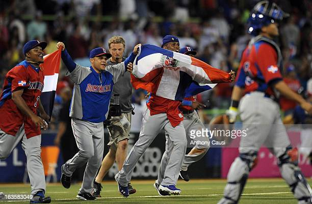 Jose Reyes and Wandy Rodriguez of Dominican Republic run out onto the field with Dominican Republic flags after defeating Puerto Rico in Pool C Game...