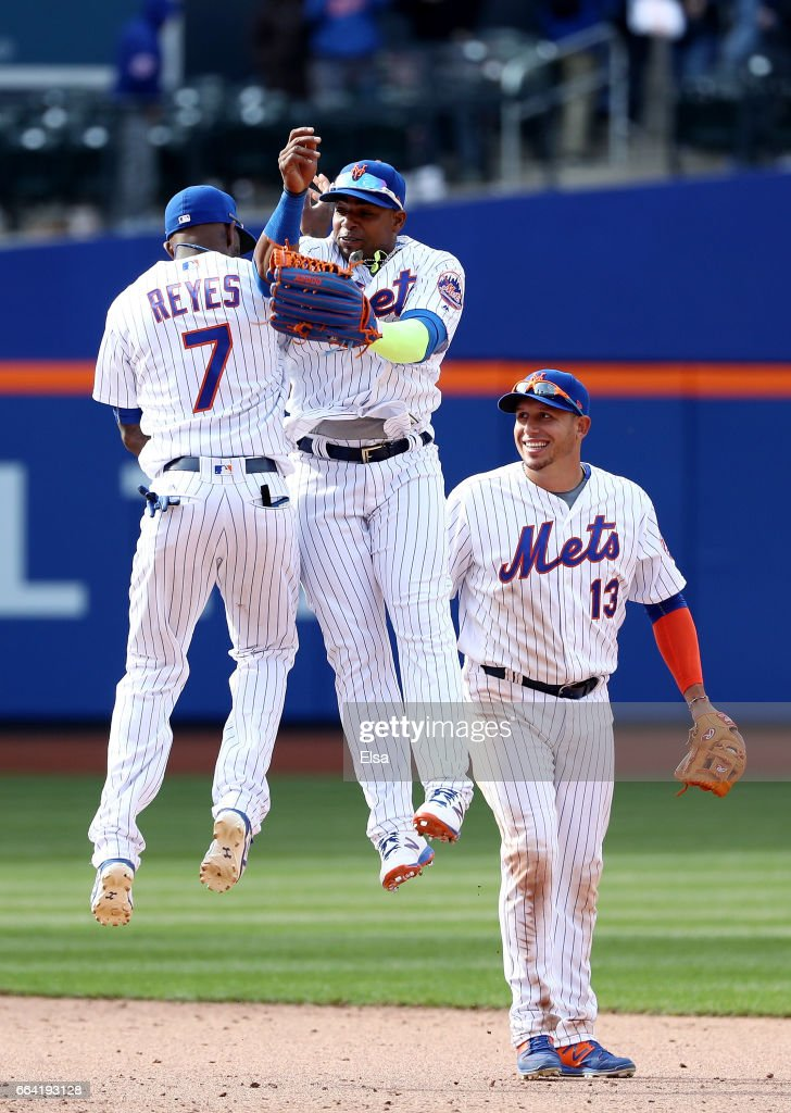 Jose Reyes #7 and Yoenis Cespedes #52 of the New York Mets celebrate the win as teammate Asdrubal Cabrera #13 looks on after the win over the Atlanta Braves during Opening Day on April 3, 2017 at Citi Field in the Flushing neighborhood of the Queens borough of New York City.The New York Mets defeated the 6-0.