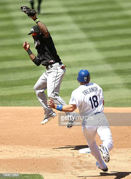 Jose Reyes of the Miami Marlins jumps to take a high throw before forcing out Matt Treanor of the Los Angeles Dodgers in the second inning on August...