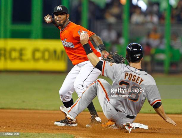 Jose Reyes of the Miami Marlins turns a double play as Buster Posey of the San Francisco Giants slides into second during a game at Marlins Park on...