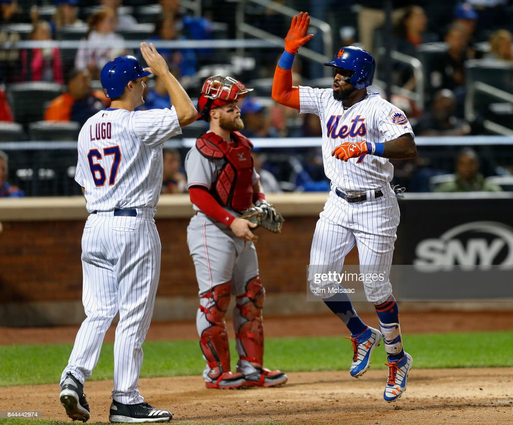 Jose Reyes #7 of the New York Mets celebrates his fifth inning two run home run with teammate Seth Lugo #67 as Tucker Barnhart #16 of the Cincinnati Reds looks on at Citi Field on September 8, 2017 in the Flushing neighborhood of the Queens borough of New York City.