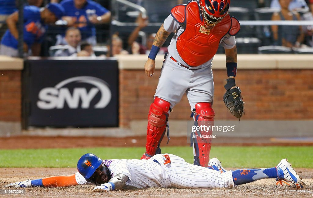 Jose Reyes #7 of the New York Mets is sprawled out at home plate after scoring in the sixth inning on his double and two errors as Yadier Molina #4 of the St. Louis Cardinals looks on at Citi Field on July 17, 2017 in the Flushing neighborhood of the Queens borough of New York City.