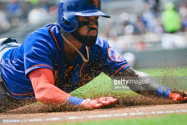 Jose Reyes of the New York Mets slides to third base during a one run line drive triple to left field against the Atlanta Braves in the first inning...