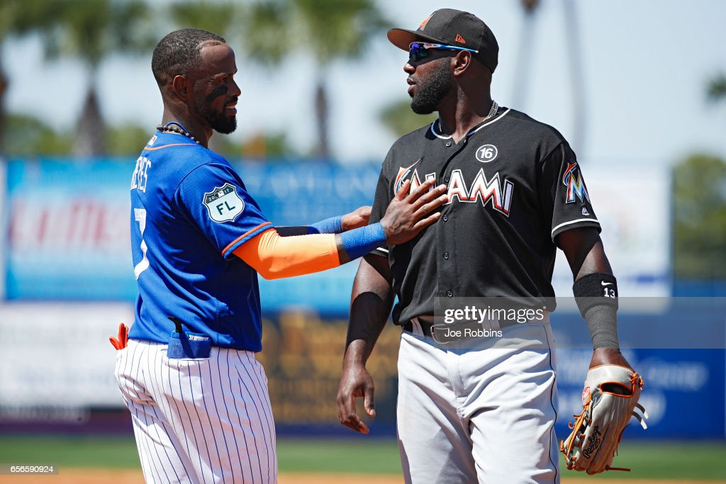 Jose Reyes #7 of the New York Mets visits with Marcell Ozuna #13 of the Miami Marlins in between innings of a Grapefruit League spring training game at Tradition Field on March 22, 2017 in Port St. Lucie, Florida. The Marlins defeated the Mets 15-9.
