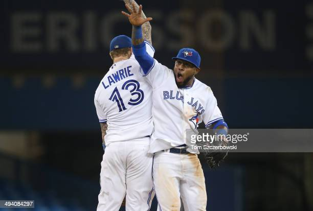 Jose Reyes of the Toronto Blue Jays celebrates their victory with Brett Lawrie during MLB game action against the Tampa Bay Rays on May 27 2014 at...