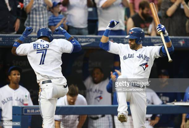 Jose Reyes of the Toronto Blue Jays celebrates with Jose Bautista after hitting a solo home run in the fifth inning during MLB game action against...