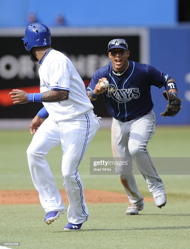 Jose Reyes #7 of the Toronto Blue Jays is caught in a run down by Yunel Escobar #11 of the Tampa Bay Rays during the first inning of MLB game action September 29, 2013 at Rogers Centre in Toronto, Ontario, Canada.