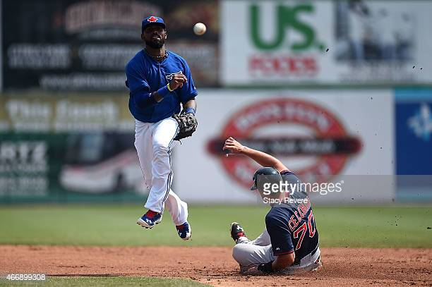 Jose Reyes of the Toronto Blue Jays makes a throw to first base to complete a double play during the second inning of a spring training game against...