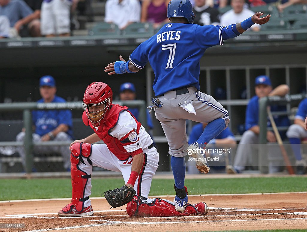 Jose Reyes #7 of the Toronto Blue Jays scores a run in the 1st inning after stepping on the leg of Adrian Nieto #17 of the Chicago White Sox who was ruled to be blocking the plate after a replay at U.S. Cellular Field on August 17, 2014 in Chicago, Illinois.