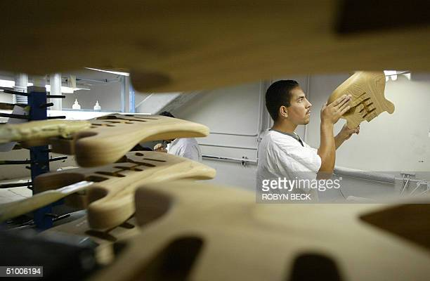 Jose Rodriguez examines his sanding work before sending Fender Stratocaster bodies to the paint shop at the Fender manufacturing facility in Corona...