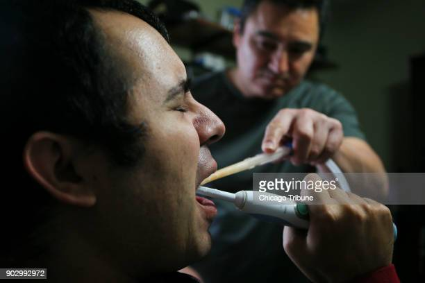 Jose Rodriguez Jr brushes his teeth while his dad Jose Rodriguez Sr suctions him at their home on Wednesday Dec 13 2017 in Aurora Ill In August of...