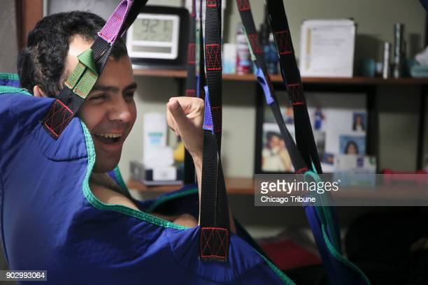 Jose Rodriguez Jr jokes as he swings from his sling at his home on Wednesday Dec 13 2017 in Aurora Ill In August of 2013 Rodriquez Jr suffered a...