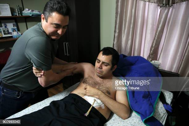 Jose Rodriguez Sr lifts his son Jose Rodriguez Jr from his bed on Wednesday Dec 13 2017 in Aurora Ill In August of 2013 Rodriquez Jr suffered a...