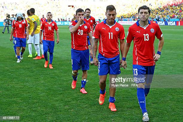 Jose Rojas and players of Chile walk off the pitch after the defeat in the 2014 FIFA World Cup Brazil Round of 16 match between Brazil and Chile at...