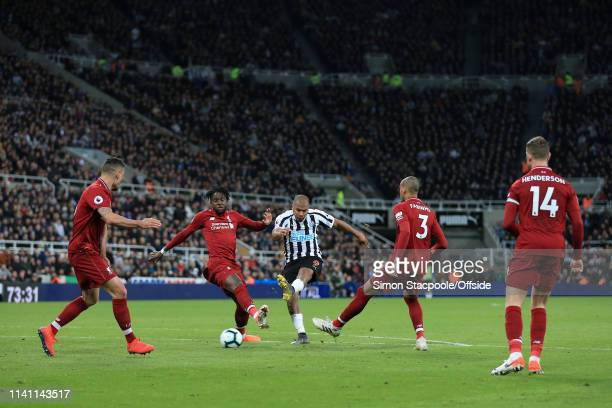 Jose Salomon Rondon of Newcastle shoots past Divock Origi of Liverpool during the Premier League match between Newcastle United and Liverpool at St...