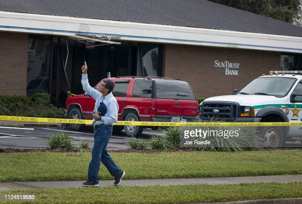 Jose Sanchez points to the sky as he walks in front of the SunTrust Bank branch where he said his friend was killed yesterday along with four other...