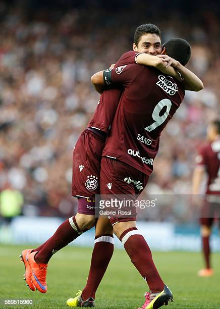 Jose Sand and Miguel Almir—on of Lanus celebrate their team's first goal scored by Brian Montenegro of Lanus during a match between Racing Club and...