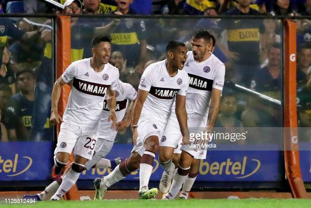 Jose Sand of Lanus celebrates his side's first goal with the teammate Rolando García and Marco Torsiglieri during a match between Boca Juniors and...