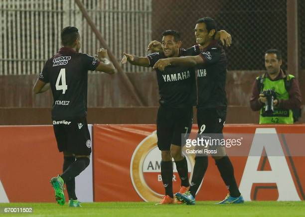 Jose Sand of Lanus celebrates with teammates Lautaro Acosta and Jose Luis Gómez after scoring the second goal of his team during a group stage match...