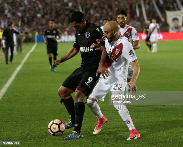 Jose Sand of Lanus fights for the ball with Javier Pinola of River Plate during a second leg match between Lanus and River Plate as part of the...