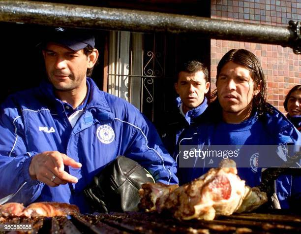 Jose Saturnino Cardozo and Jose Pablo Galdames of Mexico's Cruz Azul prepare to eat a barbecue at the Independiente Club in Buenos Aires Argentina 26...