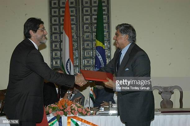 Jose Sergio Gabrielli de Azevedo Chief Executive Officer and Director of Petroleo Brasileiro SA exchanging documents with Ratan Tata Chairman of Tata...