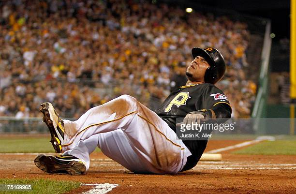 Jose Tabata of the Pittsburgh Pirates grimaces after scoring on a squeeze in the sixth inning against the Colorado Rockies during the game on August...