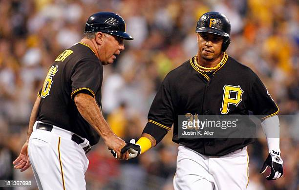 Jose Tabata of the Pittsburgh Pirates is congratulated by third base coach Nick Leyva after hitting a solo home run in the first inning against the...