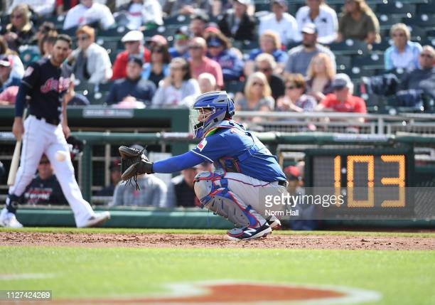 Jose Trevino of the Texas Rangers catches a warm up pitch as the pitch clock ticks down during the third inning of a spring training game against the...