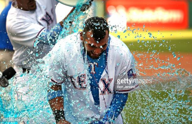 Jose Trevino of the Texas Rangers is doused by teammates after he hit a game winning tworun single against the Colorado Rockies in the bottom of the...