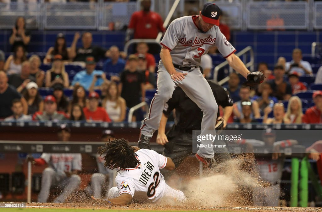 Jose Urena #62 of the Miami Marlins scores the tying run in the eighth inning sliding under the tag from Stephen Strasburg #37 of the Washington Nationals on a passed ball during a game at Marlins Park on June 21, 2017 in Miami, Florida.