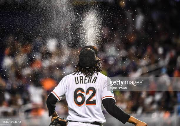 Jose Urena of the Miami Marlins sprays water heading to the pitchers mound in the fourth inning against the Washington Nationals at Marlins Park on...