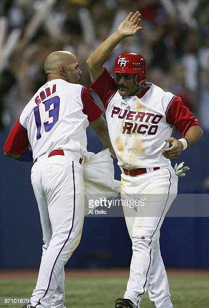 Jose Valentin of Puerto Rico celebrates with teammate Alex Cora after scoring a run against Cuba during Round 2 of the World Baseball Classic on...