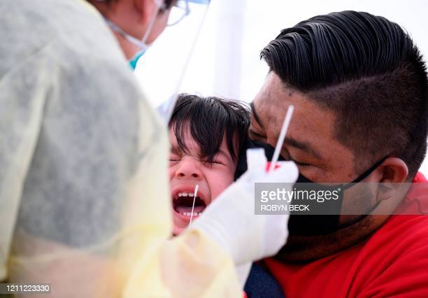 Jose Vatres holds his son Aidin who reacts as nurse practitioner Alexander Panis takes a nasal swab sample to test for COVID19 at a mobile testing...