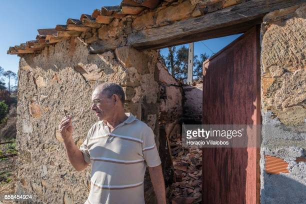 Jose Vaz da Mata holds a key while standing outside his burned barn four months after the forest fire that caused him a loss of some 15000 euros on...