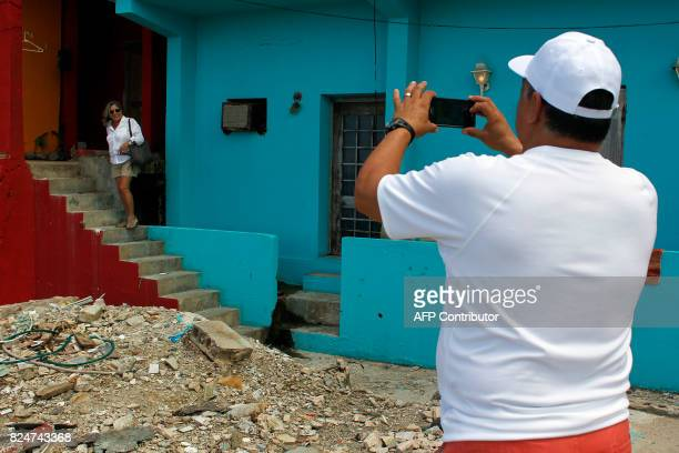Jose Vazquez takes a photo of his wife Ana Soto in the neighbourhood of La Perla where the video 'Despacito' was recorded in San Juan on July 22 2017...