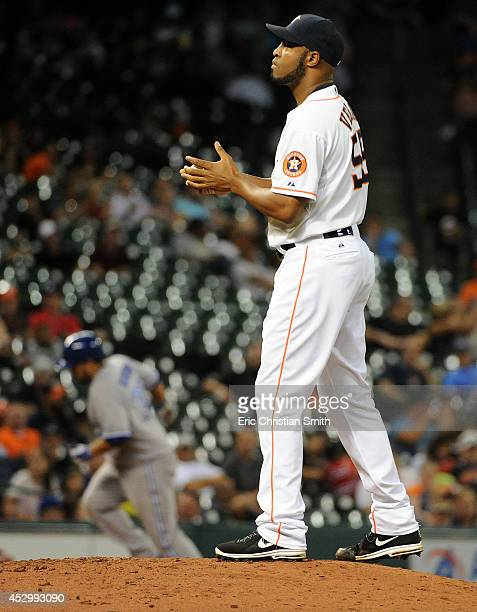 Jose Veras of the Houston Astros stands on the mound as Dioner Navarro of the Toronto Blue Jays rounds the bases after hitting a solo home run to tie...