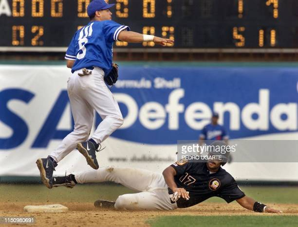 Jose Vidro from Puerto Rico sends the ball to first base after Venzuelen player Lipso Nova slides during the ninth inning of the game between Puerto...