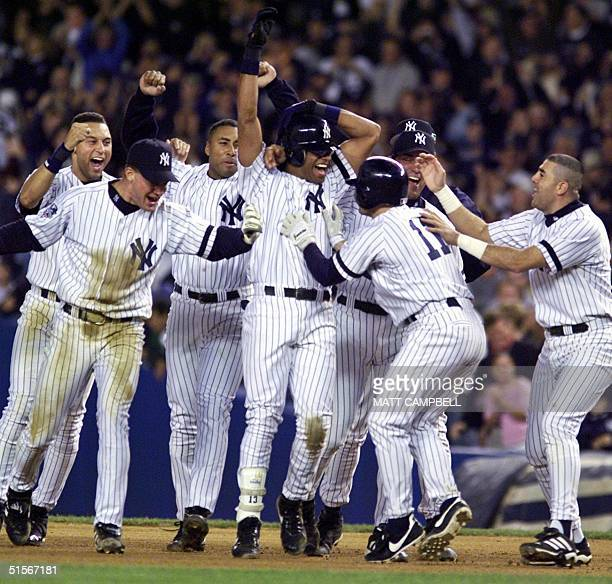 Jose Vizcaino of the New York Yankees is swarmed by teammates after his gamewinning single in the 12th inning against the New York Mets in game 1 of...
