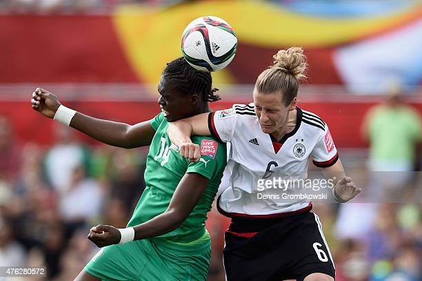 Josee Nahi of Cote D'Ivoire and Simone Laudehr of Germany go up for a header during the FIFA Women's World Cup Canada 2015 Group B match between...