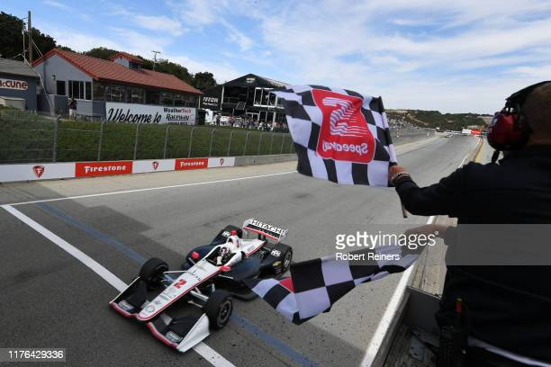 Josef Newgarden of United States and Hitachi Team Penske Chevrolet crosses the finish line to clinch the NTT IndyCar Series championship in Firestone...