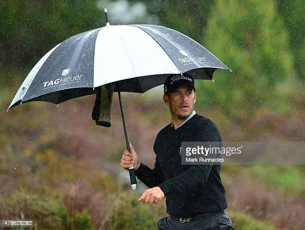 JoseFilipe Lima of Portugal takes cover under an umbrella as the rain moves in on the 13th hole during the second round of the 2015 SSE Scottish...