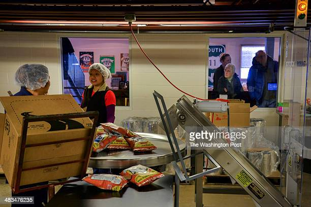 Josefina Santiago L and Liliana Santos package bags of potato chips under the watchful eyes of siblings Pam and Tim Clark of Asheville NC at Route 11...