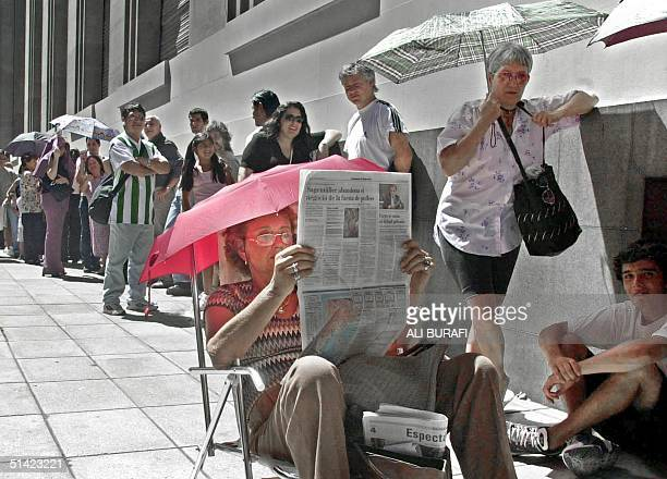 Josefina Torres reads a newspapers as she waits in a long line in front of the Banco de la Nacion Argentina to buy dollars 01 February 2002 in Buenos...
