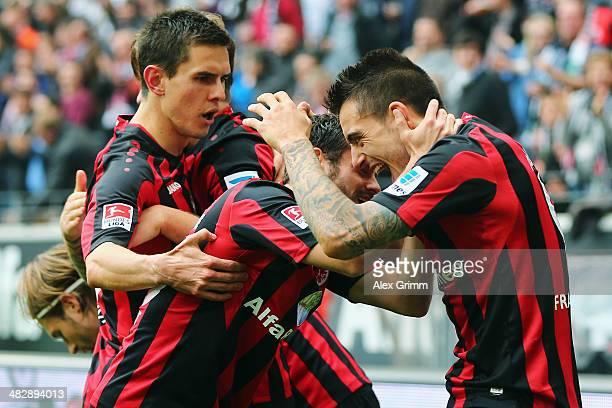 Joselu of Frankfurt celebrates his team's first goal with team mates Tranquillo Barnetta and Johannes Flum during the Bundesliga match between...
